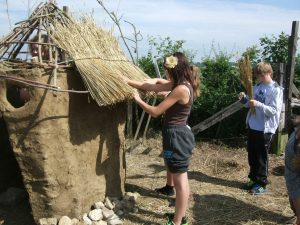 Woman repairing the thatched roof on the wattle and daub shelter near turbine two.