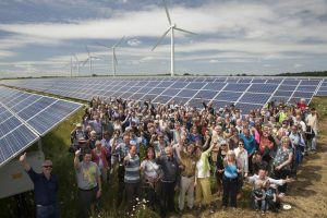 Open day visitors in front of solar panels with turbines in the background